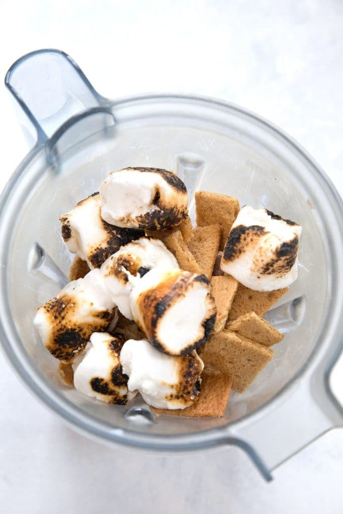 Bird's eye view of blender container containing graham crackers and toasted marshmallows