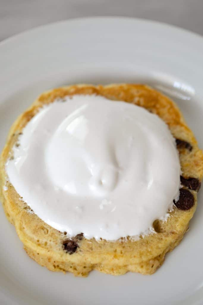 Graham cracker and chocolate chip pancakes on a plate topped with marshmallow fluff
