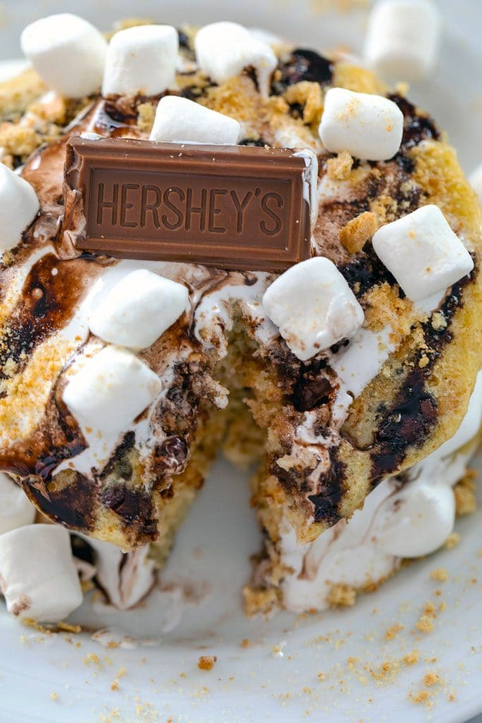 Up-close image of stack of s'mores pancakes with bite taken out and topped with mini marshmallows and a chocolate piece