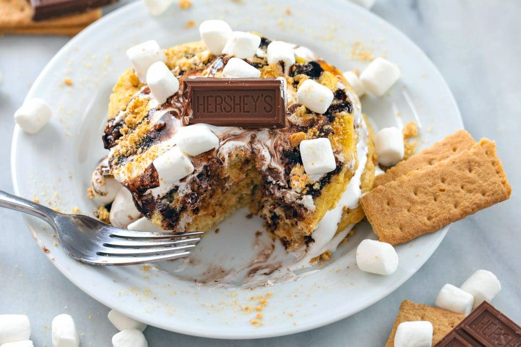 Landscape photo of stack of s'mores pancakes on a white plate with a bite taken out and topped with marshmallow fluff, chocolate sauce, mini marshmallows, chocolate pieces, and graham crackers