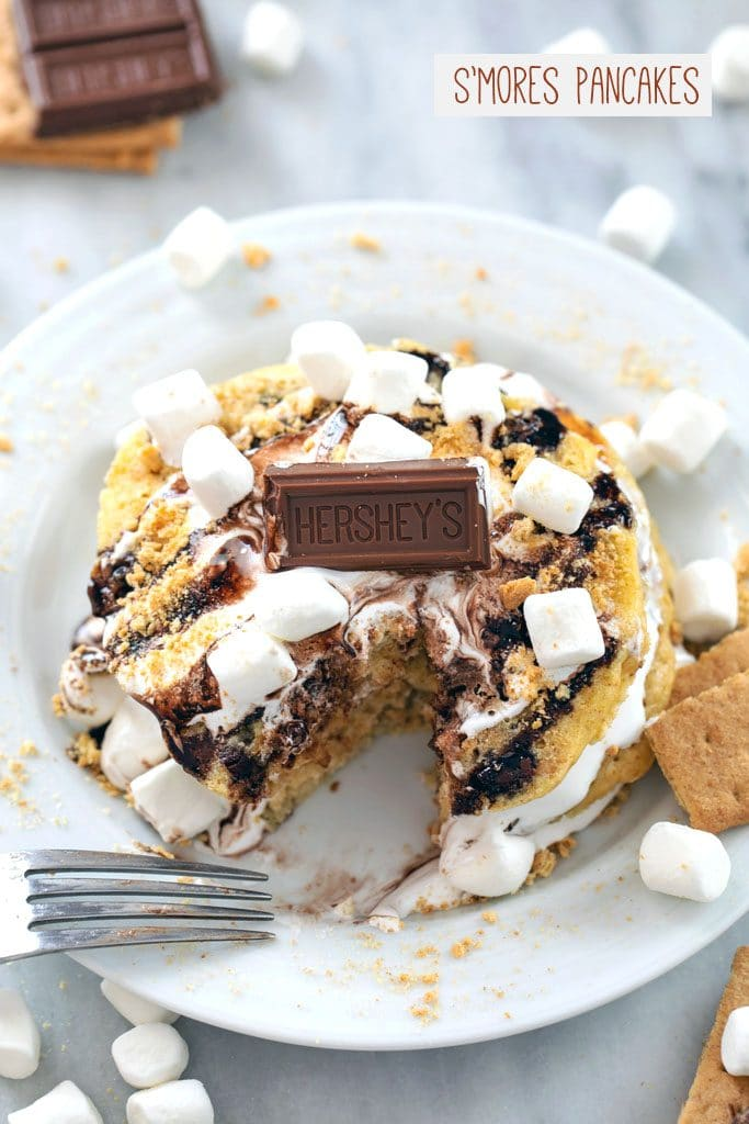 """From above view of stack of s'mores pancakes on a white plate with marshmallow fluff, chocolate sauce, mini marshmallows, chocolate bar, and graham cracker crumbs with """"S'mores Pancakes"""" text at top"""