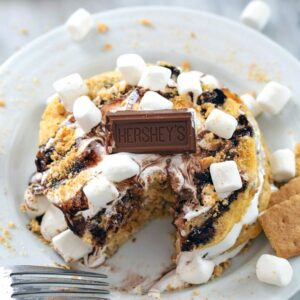 S'mores Pancakes -- Whether you need a little Sunday morning indulgence or are taking breakfast for dinner to new levels, these S'mores Pancakes packed with graham cracker flavor, homemade marshmallow fluff, and chocolate sauce are sure to make your whole family happy | wearenotmartha.com