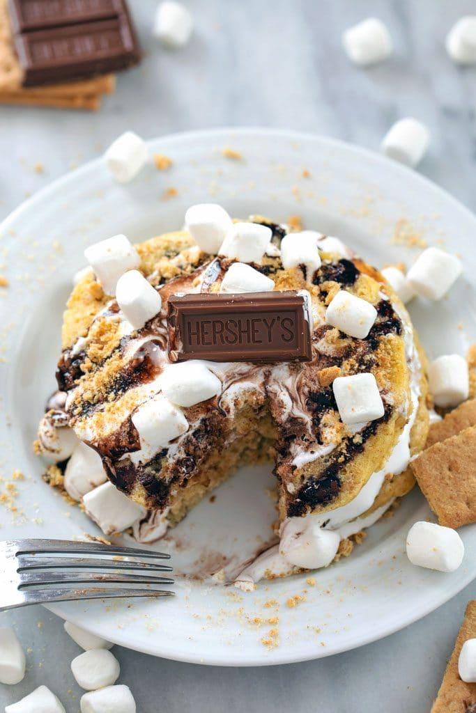 From above view of stack of s'mores pancakes on a white plate with marshmallow fluff, chocolate sauce, mini marshmallows, chocolate bar, and graham cracker crumbs