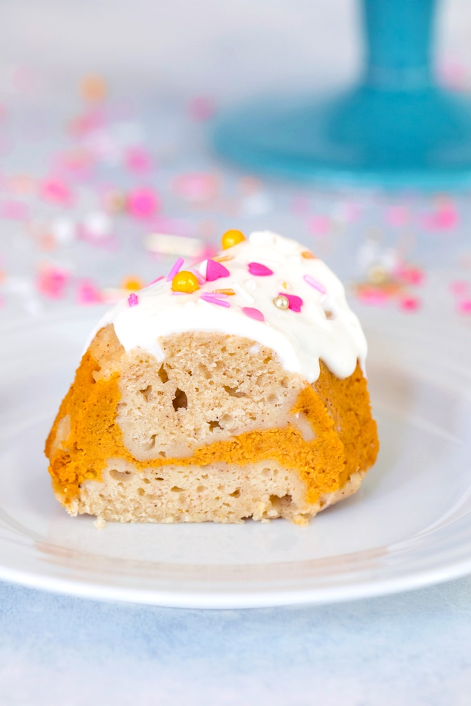 Head-on view of a slice of sour cream pumpkin pie bundt cake with pumpkin swirl and pink and orange sprinkles on a white plate with sprinkles in the background