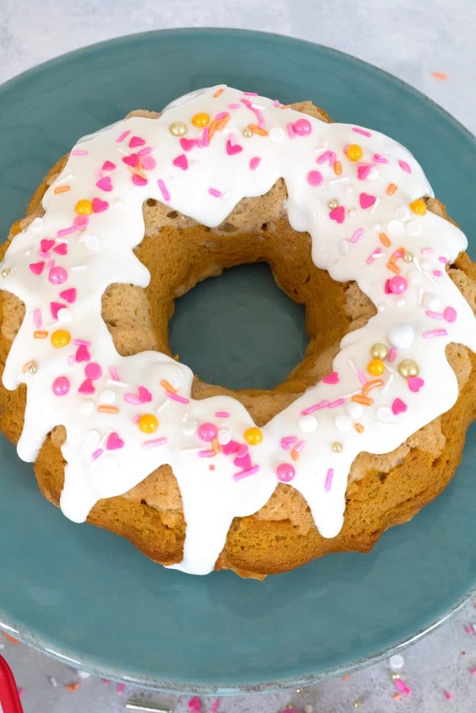 Overhead view of sour cream pumpkin pie bundt cake with white icing and pink and orange sprinkles on a teal cake stand