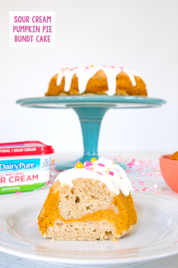Head-on view of a slice of sour cream pumpkin pie bundt cake with pumpkin swirl and pink and orange sprinkles on a white plate with sprinkles in the background with recipe title at top