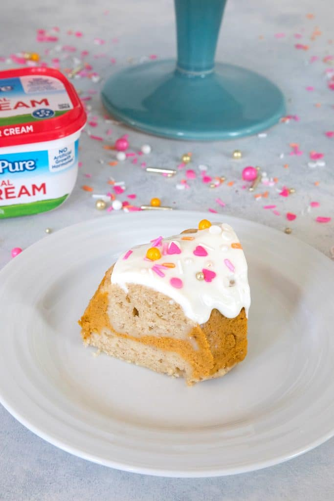 Overhead view of a slice of sour cream pumpkin pie bundt cake with pink and orange sprinkles on a white plate with a sour cream container and cake stand in background
