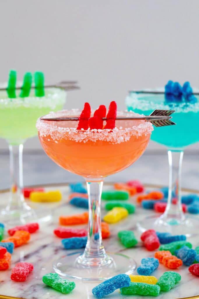 Head-on view of red Sour Patch Kids margarita with green and blue drinks in background all with Sour Patch Kids garnish and candies all around