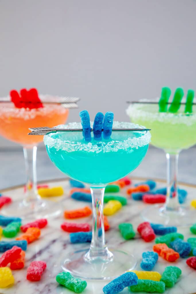 Head-on view of a blue Sour Patch Kids margarita with Sour Patch Kid garnish with a red and green cocktail in background and Sour Patch kids all around