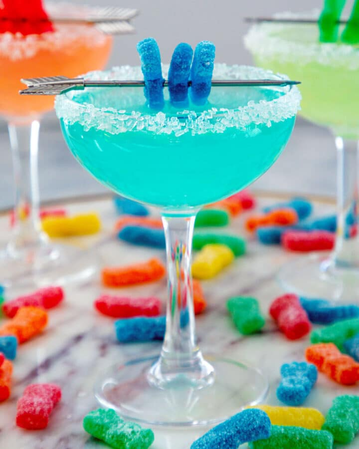 Head-on view of blue Sour Patch Kids margarita with two more cocktails in background and candies all around
