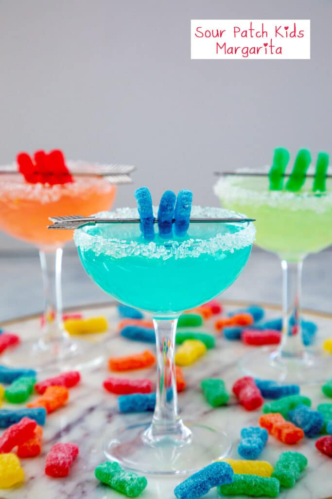 Head-on view of a blue Sour Patch Kids margarita with Sour Patch Kid garnish with a red and green cocktail in background and Sour Patch kids all around and recipe title at top