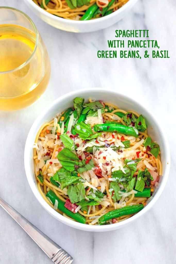 Overhead view of a bowl of spaghetti with pancetta, green beans, and basil on a marble surface with glass of white wine, fork, and second bowl of pasta in background with recipe title at top