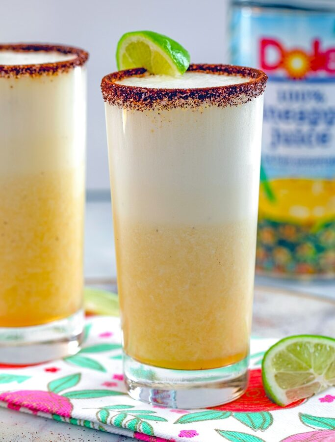 Spiced Pineapple Cocktail -- This Spiced Pineapple Cocktail is a tequila-based drink packed with fresh pineapple and pineapple juice, a little bit of citrus, and a spicy kick from the spiced rim of the glass | wearenotmartha.com