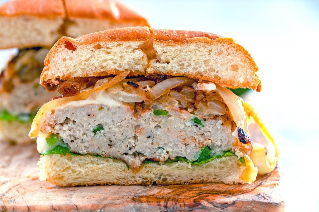 Landscape view of a spicy cheesy chicken burger with caramelized onions cut in half on wooden cutting board