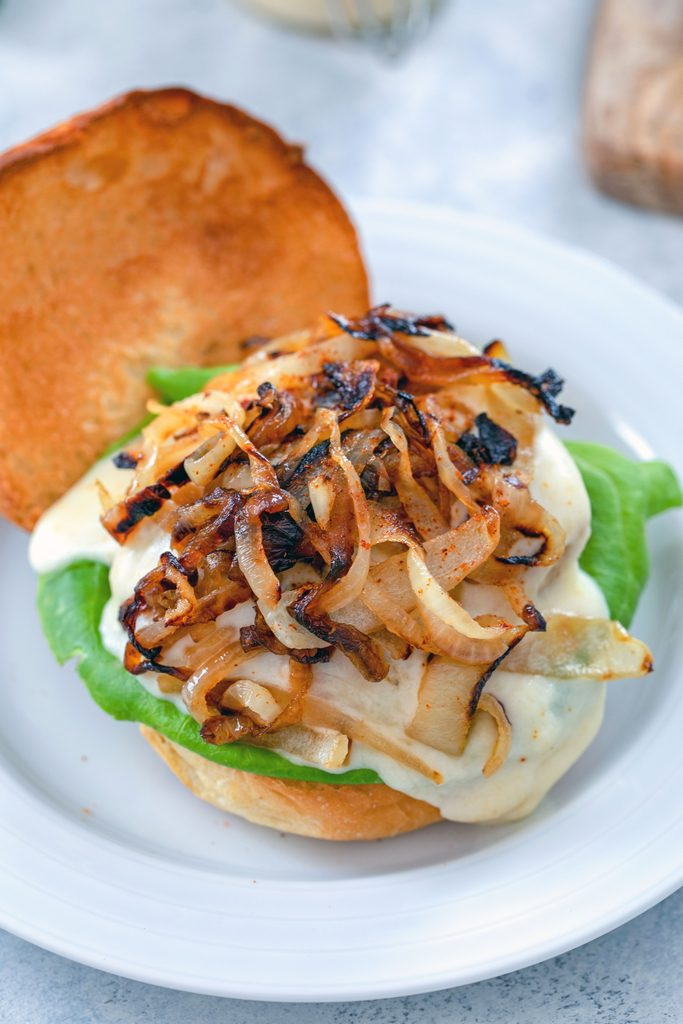 Overhead view of open-faced spicy cheesy chicken burger on brioche roll topped with lettuce, cheese sauce, and caramelized onions