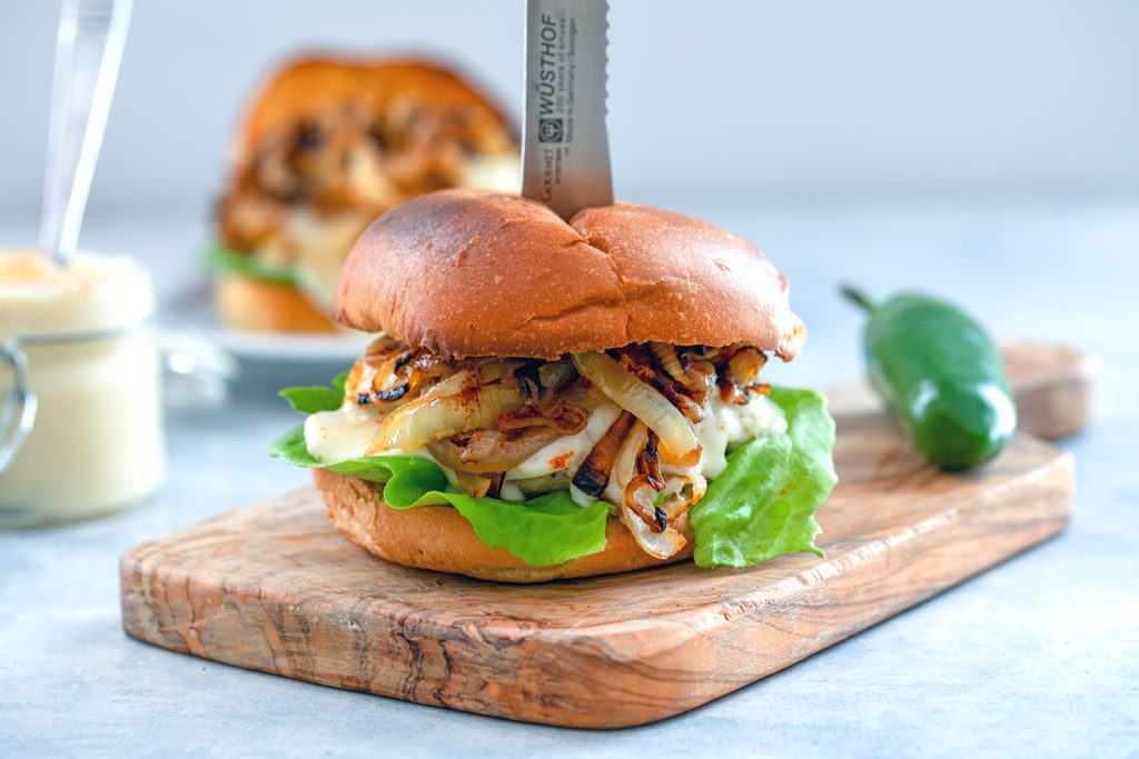 Landscape view of spicy cheesy chicken burger with cheese sauce and caramelized onions with a knife stuck in it on a small wooden cutting board with jar of cheese sauce, second burger, and jalapeño pepper in background