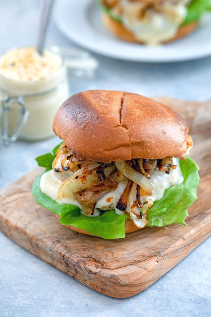 Head-on view of spicy cheesy chicken burger with caramelized onions on a small wooden cutting board with jar of cheese sauce and second burger in the background