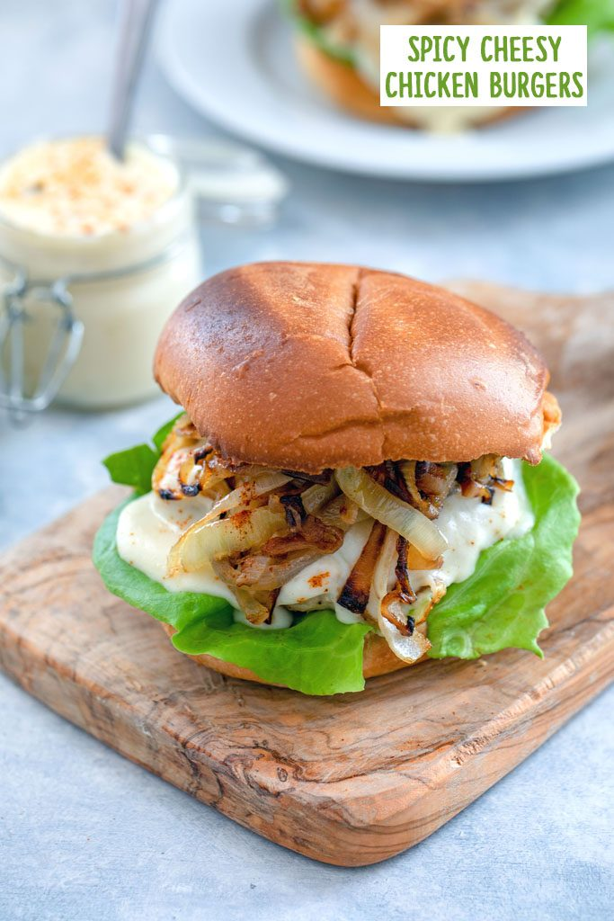 Head-on view of spicy cheesy chicken burger with caramelized onions on a small wooden cutting board with jar of cheese sauce and second burger in the background with recipe title at top