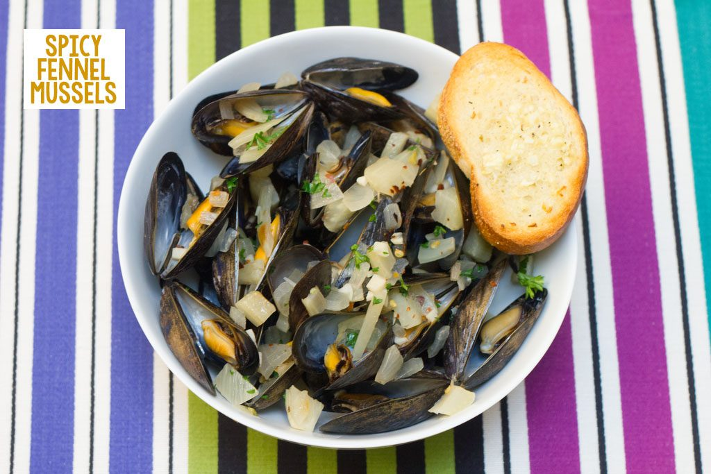 Overhead view of spicy fennel mussels in a white bowl with a side of garlic bread on a colorful striped placemat with recipe title at top