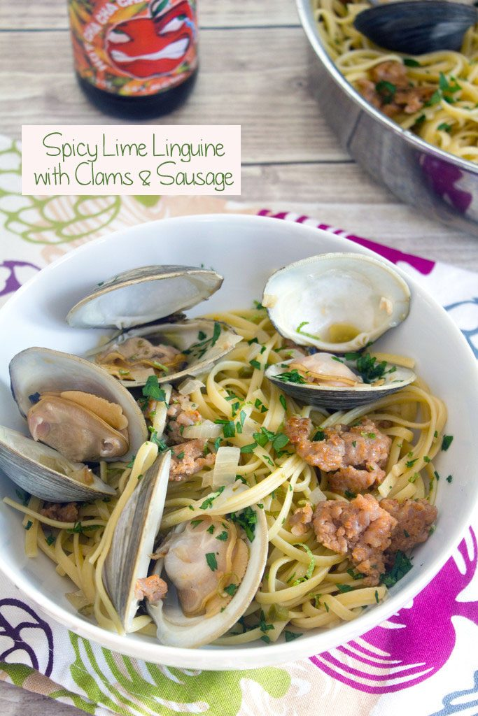 Overhead view of a big bowl of spicy lime linguine with clams and sausage with a hard cider in the background and recipe title at top