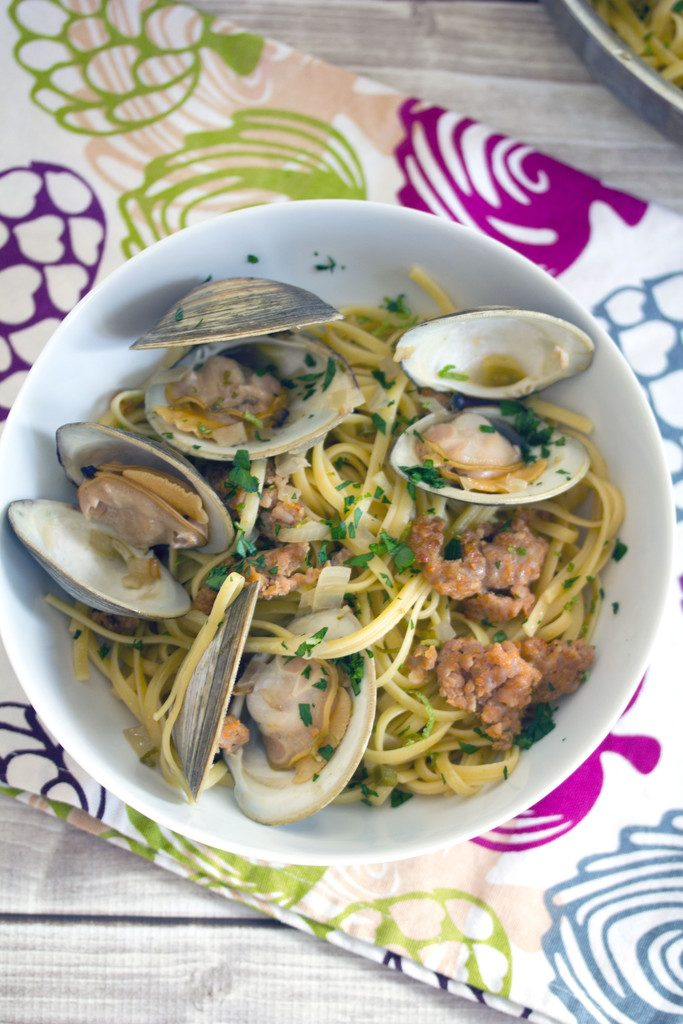 Bird's eye view of a white bowl of spicy lime linguine with clams and sausage on a colorful tea towel