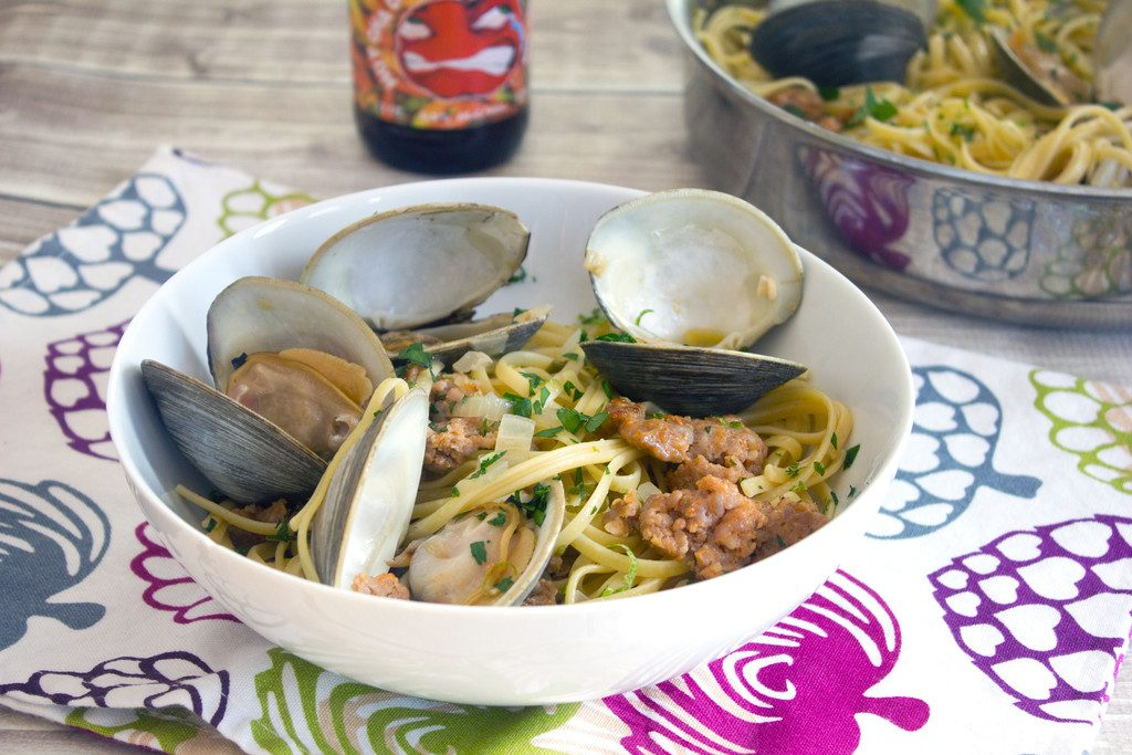 Landscape head-on view of a big white bowl of spicy lime linguine with clams and sausage on a colorful tea towel with bottle of cider and pan of linguine and clams in the background