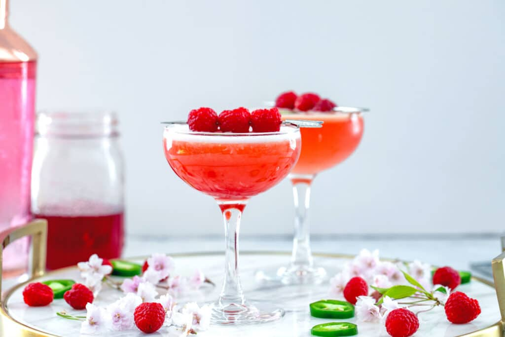 Landscape head-on view of two spicy raspberry whiskey sours on a marble tray with raspberry simple syrup and pink shaker in background and raspberries, sliced jalapeños, and flowers all around
