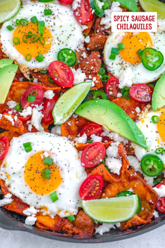 Overhead closeup view of spicy sausage chilaquiles with fried eggs, avocado, tomato, jalapeño, lime, and scallions with recipe title at top
