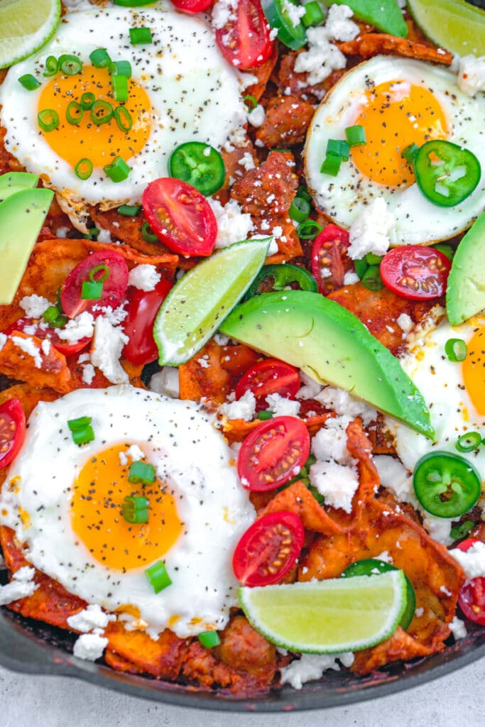 Overhead closeup view of spicy sausage chilaquiles with fried eggs, avocado, tomato, jalapeño, lime, and scallions