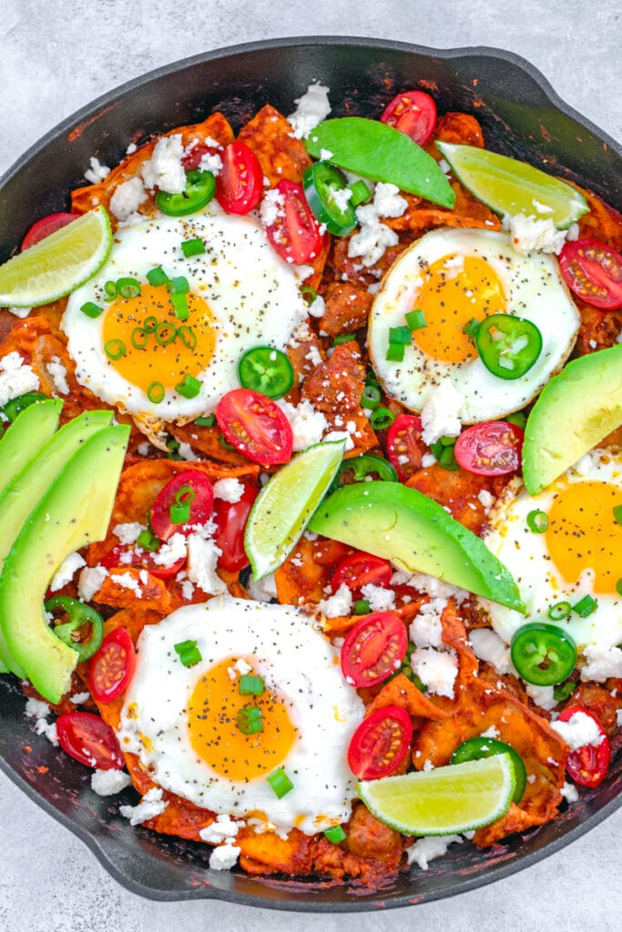 Overhead view of skillet with spicy sausage chilaquiles with eggs, avocado, sliced tomatoes, sliced jalapeño, lime wedges, and scallions