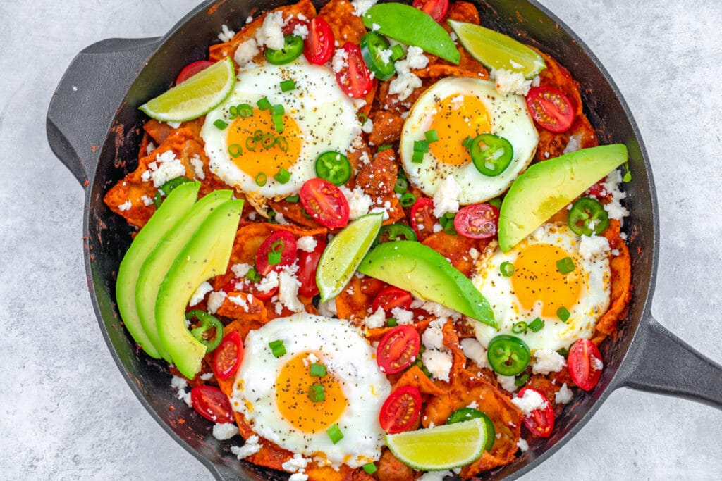 Landscape bird's eye view of skillet of spicy sausage chilaquiles with fried eggs, sliced avocado, tomatoes, scallions, lime wedges, and sliced jalapeños.