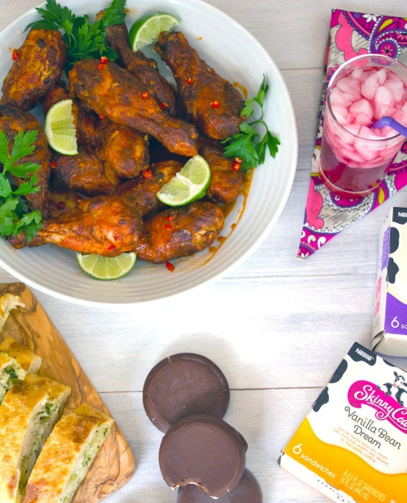 Bird's eye view of white serving bowl filled with spicy Thai chicken drumsticks, glass of berry juice, garlic bread, and ice cream sandwiches