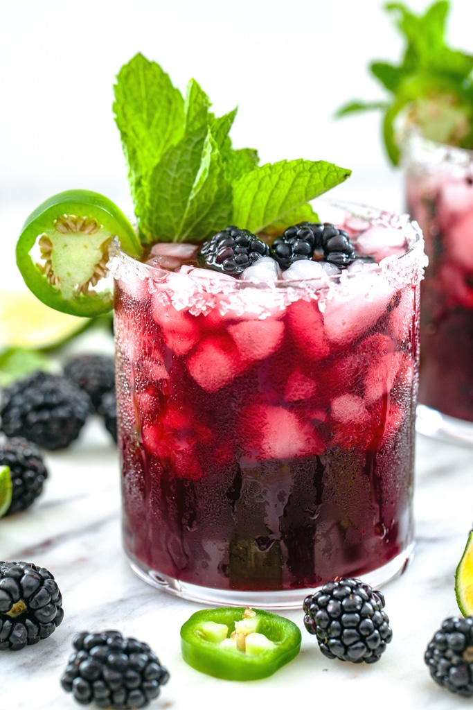 Spicy vodka blackberry smash cocktail with blackberries and jalapeño slices all around and jalapeño and mint garnish
