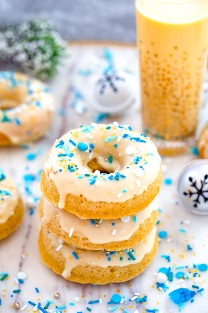 Head-on view of a stack of three spiked eggnog doughnuts with more doughnuts, glass of eggnog, jingle bells, and blue and white sprinkles in background