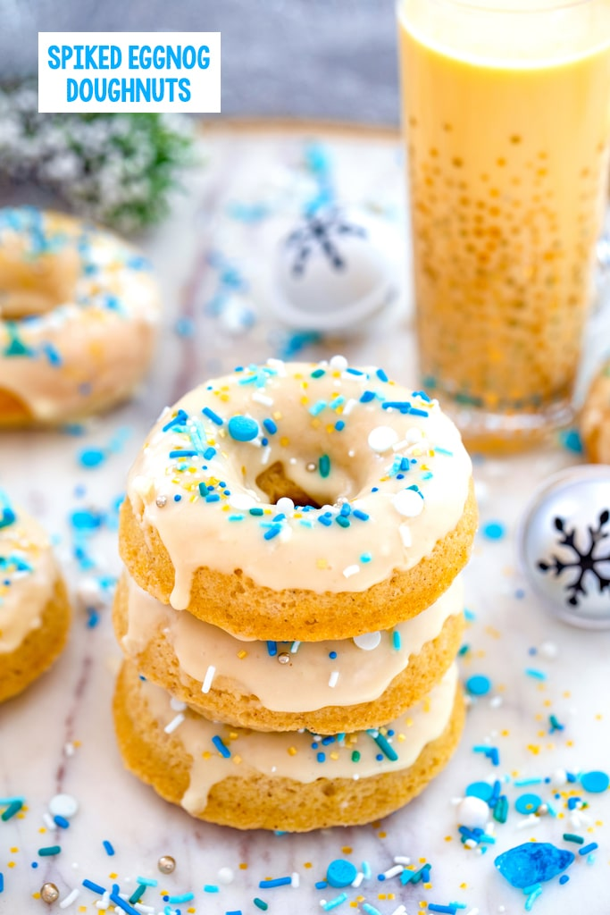 Head-on view of a stack of three spiked eggnog doughnuts with more doughnuts, glass of eggnog, jingle bells, and blue and white sprinkles in background with recipe title at top