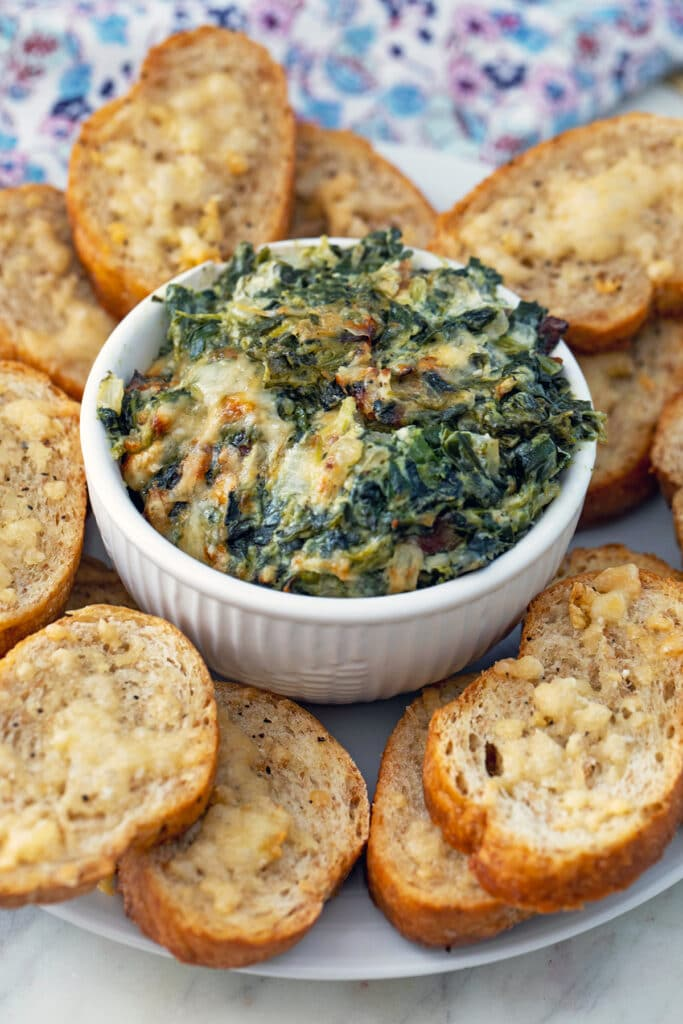 View of spinach dip with onion and bacon in a bowl surrounded by garlic toasts