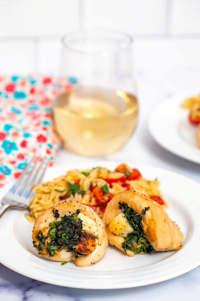 Two spinach and brie-stuffed chicken rollups with tomato orzo with fork and glass of white wine in the background