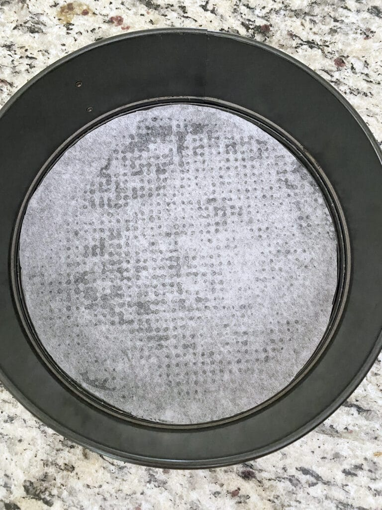 Overhead view of a round springform pan with parchment paper in it
