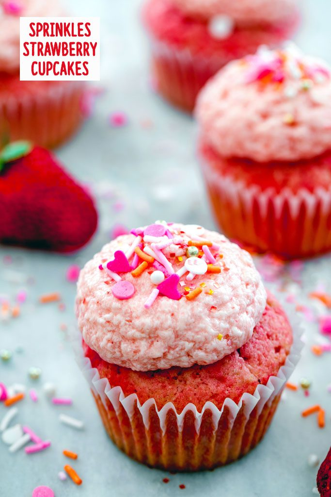Overhead view of multiple Sprinkles strawberry cupcakes on a marble surface with pink and orange sprinkles and strawberries in the background and recipe title at top
