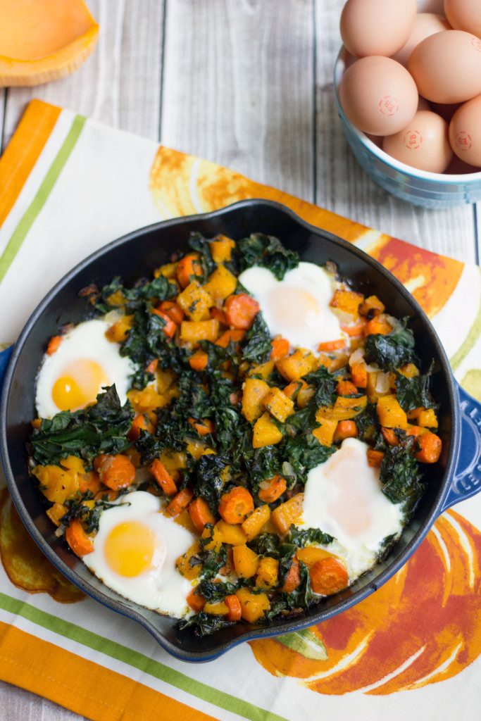 Bird's eye view of a cast iron skillet with squash hash with kale and eggs with half a butternut squash and bowl of eggs in the background