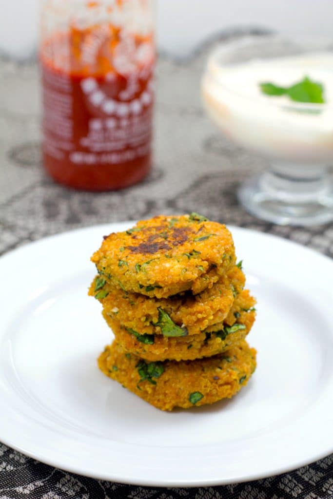 Head-on view of four sriracha quinoa cakes stacked on a white plate with bottle of sriracha and yogurt dipping sauce in background