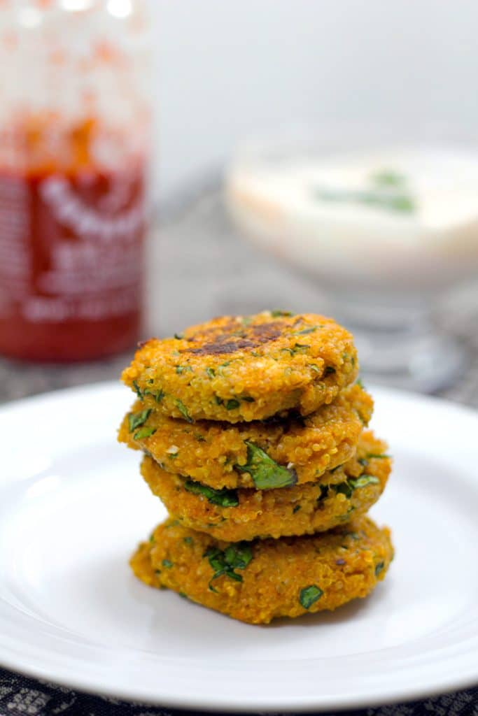 Head-on closeup view of four sriracha quinoa cakes stacked on each other on a white plate with a bottle of sriracha and yogurt dipping sauce in the background with recipe name at the top