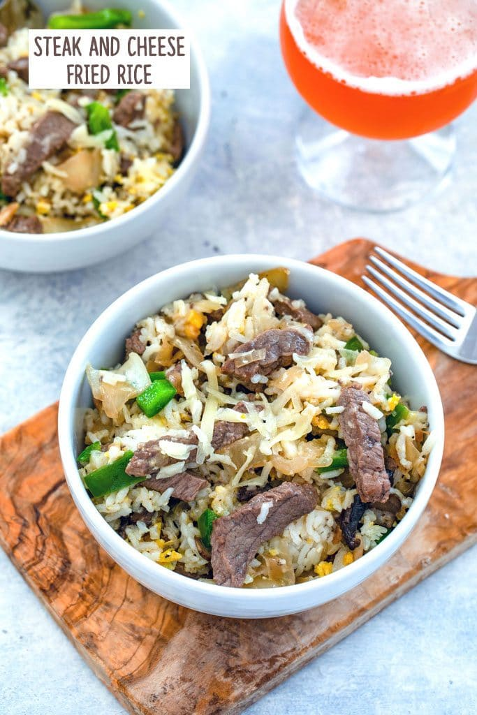 Bird's eye view of bowl of steak and cheese fried rice on a wooden board with fork, second bowl, and glass of beer in the background with recipe title at top