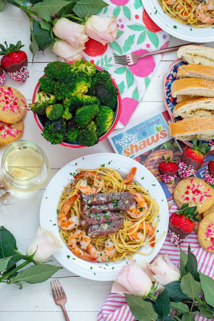 Overhead view of Valentine's Day spread with bowl of steak and shrimp scampi surrounded by roses, cookies, chocolate-covered strawberries, garlic bread, broccoli, and glass of wine