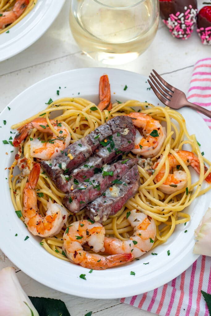 Overhead view of steak and shrimp scampi in a white bowl  with fork and white wine