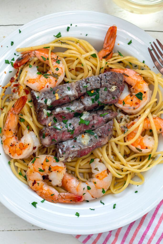 Overhead closeup view of steak and shrimp scampi in white bowl