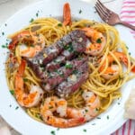 Close-up view of steak and shrimp scampi in a white bowl