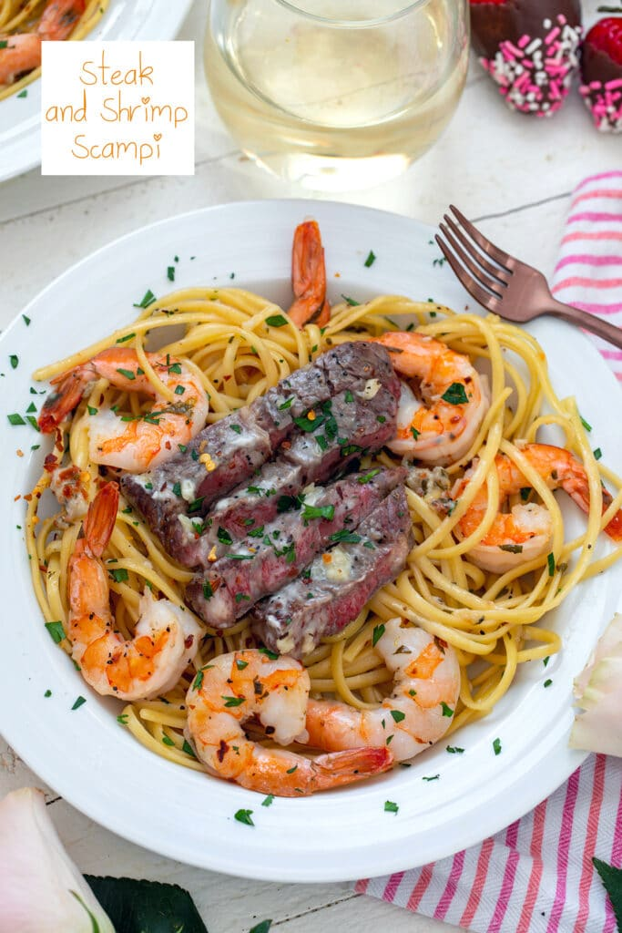 Overhead view of steak and shrimp scampi in a white bowl  with fork and white wine and recipe title at top