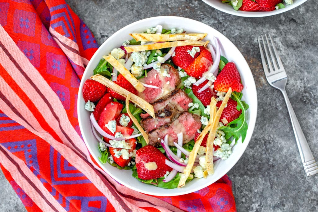 Landscape view of steak and strawberry salad in white bowl with fork next to it