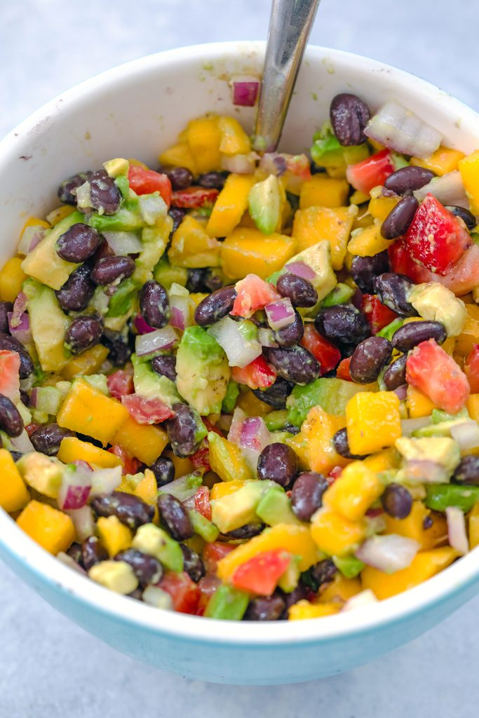Overhead view of bowl of fruit salsa with chopped mango, strawberry, avocado, red onion, and black beans